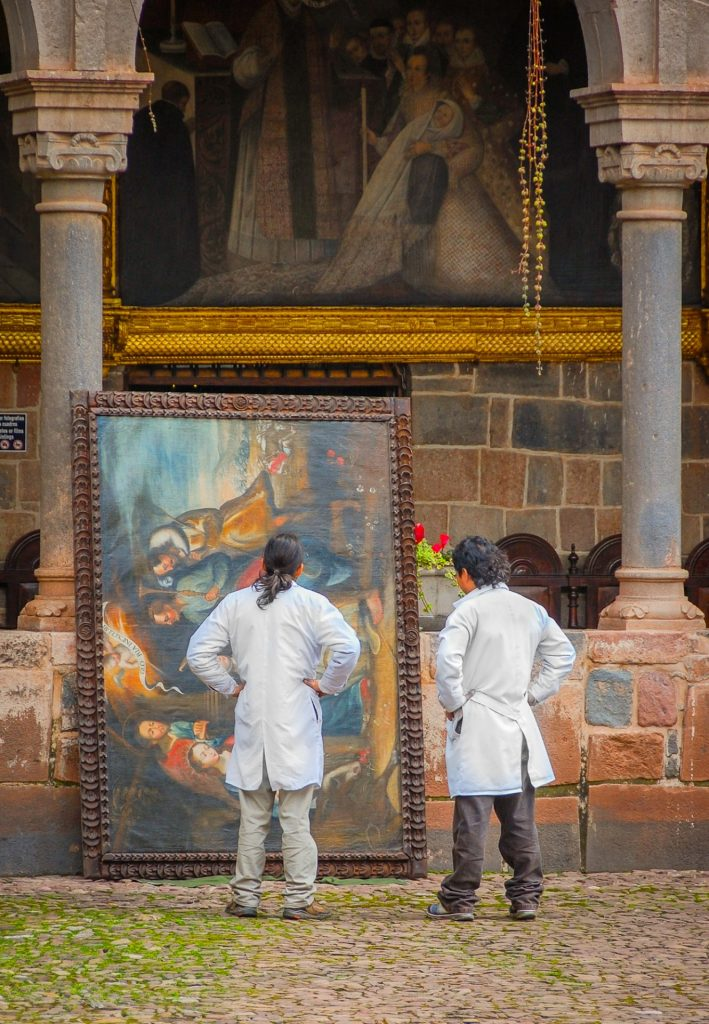 Travel and Creativity: Art restorers viewing painting in Cuzco, Peru